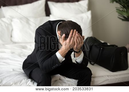 Stressed upset man in formal suit sitting on bed with hands on his head, having headache or migraine. Person in despair. Business deal went wrong, financial loss, got fired, not feeling well concept.