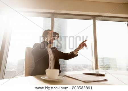 Businessman in VR headset glasses pointing finger in air. Office worker or CEO immersed in virtual reality, innovative method of browsing web or managing business project through augmented reality.