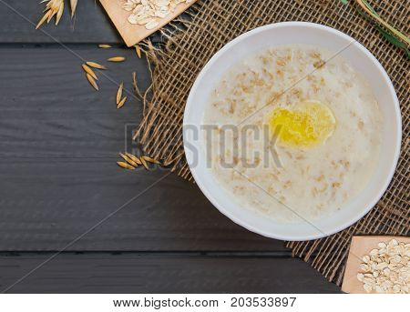 Porridge from oat flakes in a white dish, healthy Breakfast, on wooden table, top view, with natural grains and cereals oat, closeup