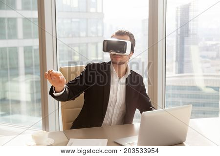 Businessman in VR headset glasses pointing finger in air. Office worker or CEO immersed in virtual reality, innovative method of browsing web or managing business project through augmented reality ar.