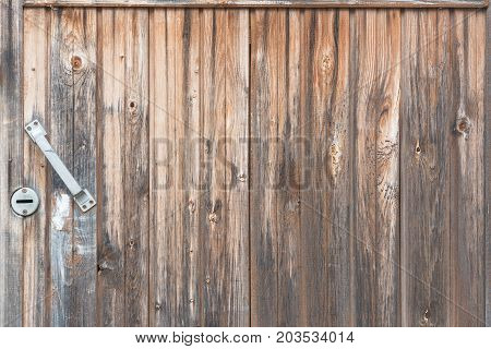 Background in style a rustic from old vertical wooden unpainted boards with a with the handle and a keyhole