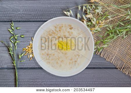 Porridge from oat flakes in a white dish, healthy Breakfast, on wooden table, top view, with natural grain, spikelets and cereals oats, closeup