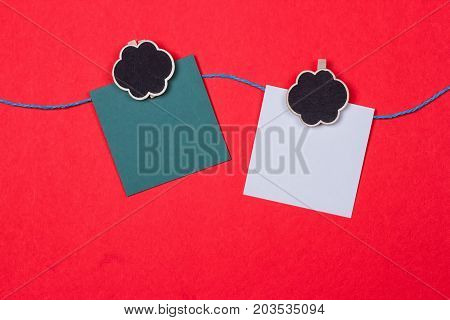 Clothespins papers with a place for writing on a red background