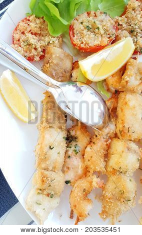 fish skewers with tomatoes gratinated and salad