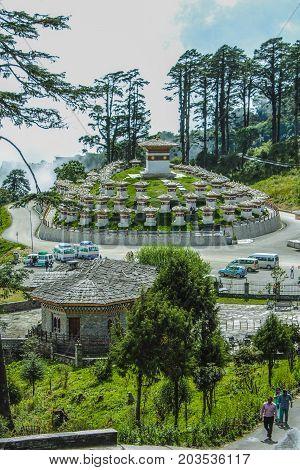 Thimphu Bhutan - September 10 2016: Druk Wangyal Khangzang Stupa with 108 chortens Dochula Pass Bhutan. Tourists on the stairs.