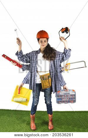 Smart Girl With Six Hands Stands On The Green Grass And Holds Building Tools. Building Concept With