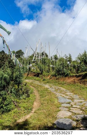Walkway with prayer flags near Druk Wangyal Khangzang Stupa with 108 chortens Dochula Pass Bhutan. Dochula pass is located on the way to Punakha from Thimphu.