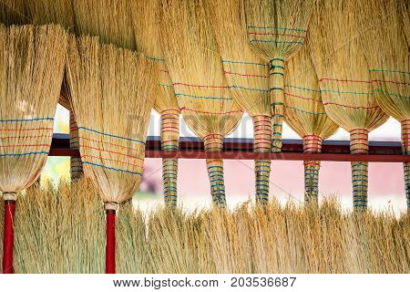 Close up rows of straw brooms for sale on market