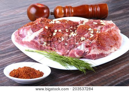 Raw pork steaks on wooden board with herbs, spices and tomatoes ready for cooking. Selective focus