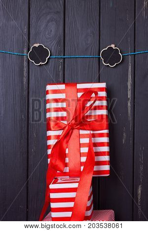 Gift box with a red bow on a wooden background With clothes pegs and place for text