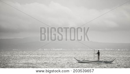 black and white photo of lone boatman at sea