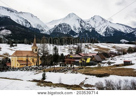 Church and cemetery in Zdiar village with Belianske Tatry mountains Slovak republic. Winter holiday resort.