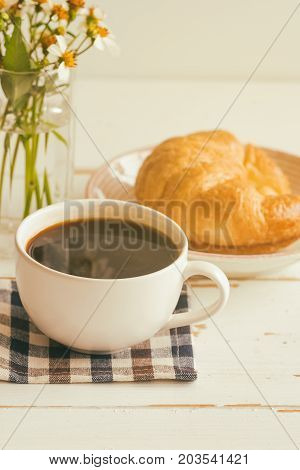 Black coffee or americano served with homemade croissant on plate. Delicious and quick breakfast with fresh croissant and coffee. Croissant and black coffee for breakfast on wood table in vertical. Coffee break with delicious croissant.