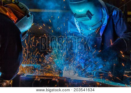Industrial workers with protective mask are welding automotive part