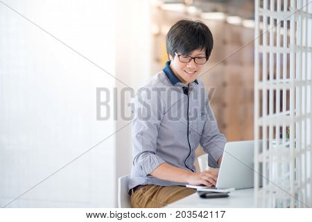 Young Asian man dressed in casual style working in cafe with his laptop computer. Digital nomad and IT modern lifestyle Co working space for freelance jobs