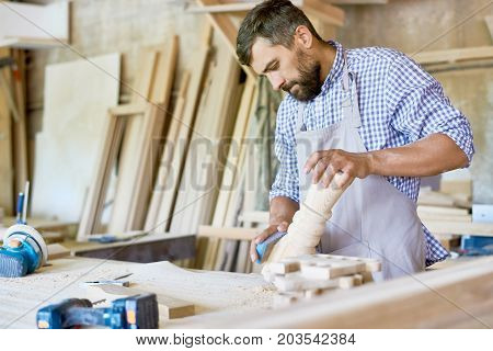 Confident bearded carpenter in checked shirt and apron polishing wooden detail with sandpaper, interior of messy workshop on background