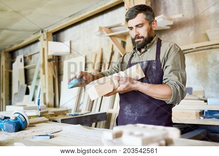 Handsome bearded craftsman using sandpaper in order to remove paint from wooden detail, interior of spacious workshop on background