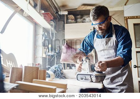 Confident bearded carpenter wearing apron and safety goggles working with belt sander, interior of messy workshop on background