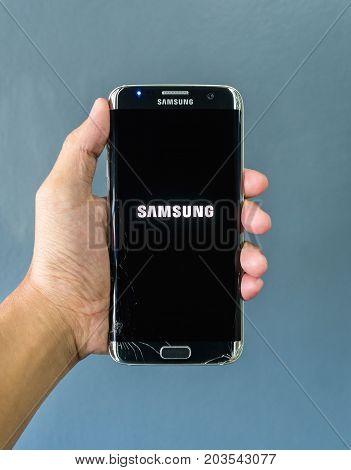 Chiangrai Thailand: September 2 2017 - Human hand holding broken Samsung Galaxy S7 edge smartphone and showing logo 'SAMSUNG' on screen