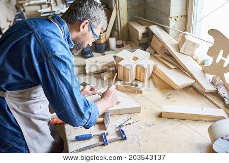 Profile view of bearded carpenter in denim shirt measuring wooden plank with ruler and pencil, messy table covered with sawdust
