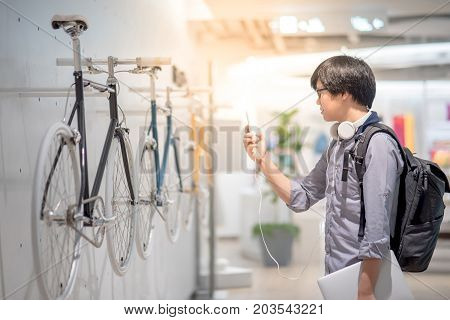 Young Asian man take a photo of vintage bicycle at bike shop in department store by his smartphone urban lifestyle concept