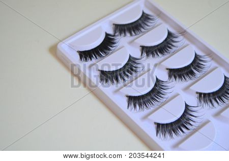 Long black false eyelashes in a package on a white background