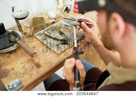 Portrait of young man welding  metal at table in workshop