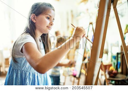 Profile view of pretty little girl wearing striped dress embodying her ideas on canvas with help of paintbrush and watercolors, interior of art studio on background