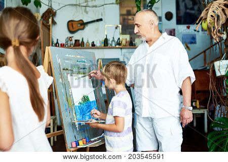 Experienced bearded teacher helping little boy to draw on canvas with watercolors, unrecognizable female pupil looking at them with interest, interior of art studio on background