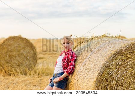 Young Girl On Straw Sheaves In A Field