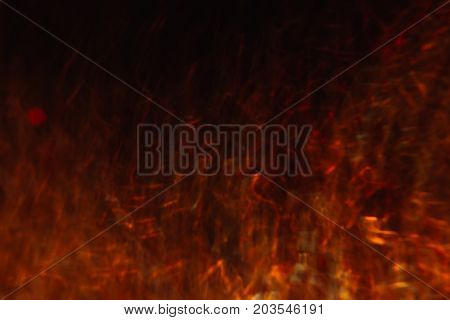Abstract background of colorful crankles in motion on black. Bokeh of defocused curves, blurred neon yellow and red leds, hellfire and heat haze, abyss and seven circles of hell