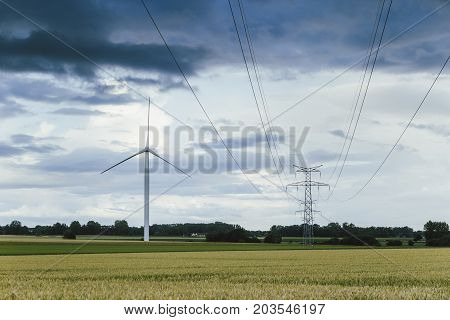 Wind Turbines For Electrical Power Generation And Power Lines In Green Field On Cloudy Day In Norman