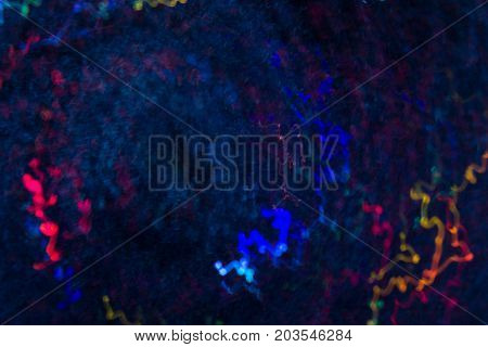 Abstract background of colorful waves in motion on black. Bokeh of defocused curves, blurred neon blue, yellow and purple leds, similar to microorganisms in humans body, medicine and biology