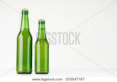 Set of two green longneck beer bottles 330ml mock up. Template for advertising design branding identity on white wood table.