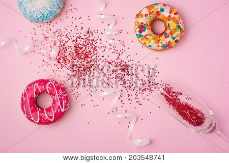 Flat Lay Of Celebration. Champagne Glass With Colorful Party Streamers And Delicious Donuts On Pink