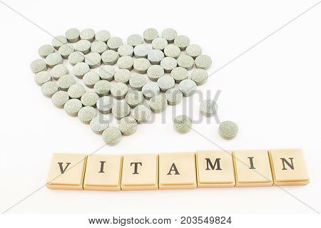 Heart made of spirulina pills and ''vitamins'' written with tokens. Concept of health. White background.