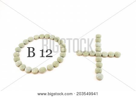 Contour of a circle and the plus sign made up of spirulina pills with word B12 inside. Supplement of vitamin B12. White background.