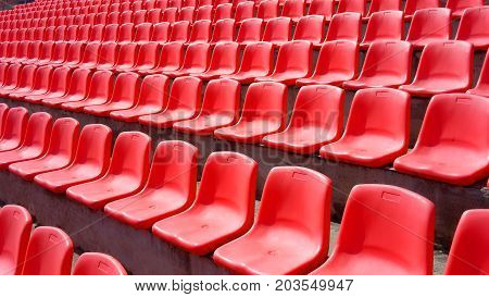 Many red plastic seats grandstand stadium in the fresh air day and light view angle