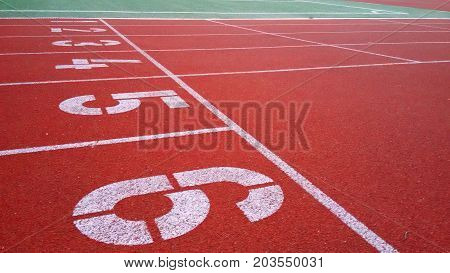 Start numbering Jogging sports rubberized red track stadium on the street selective focus