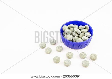 Container blue with spirulina pills. White background.