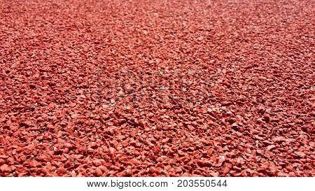 Sport Perspective Background. Decorative coating at the stadium in outdoor. Modern street red elastic rubber coating for running tracks and athletic fields in close proximity