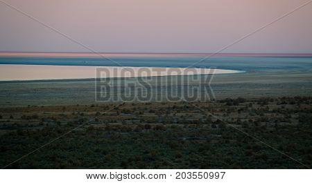 Panorama view to Aral sea from the rim of Plateau Ustyurt near Aktumsuk cape at sunset in Karakalpakstan, Uzbekistan