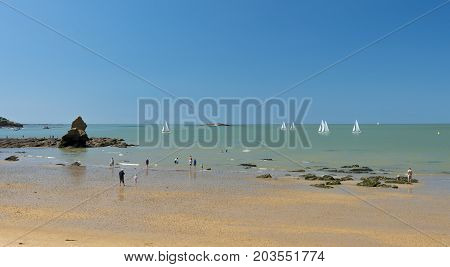 Sailing boats glide by on a hot summer day at a South Brittany beach in the Gulf of Morbihan
