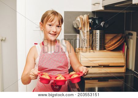 Happy little kid girl holding tray of freshly baked muffins cooking with children