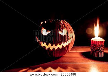 Spooky smiling halloween pumpkin with burning fire candle flame. The big helloween symbol has a mad face glowing eyes mouth and teeth glow. Black orange nightmare of October 31st on wooden table. poster