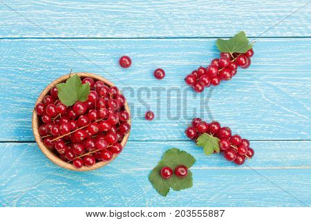Red currant berries in a wooden bowl with leaf on the blue wooden background. Top view.