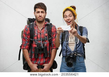 Female And Male Backpackers: Dissatisfied Male Holding Huge Rucksack And Binoculars Looking Tired, P