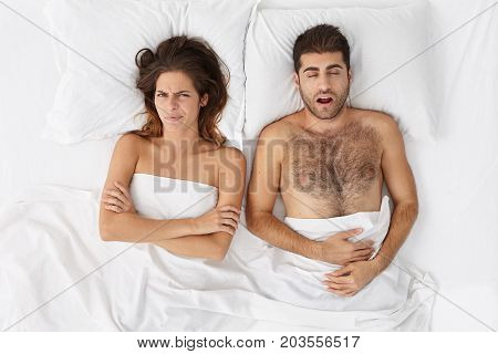 Young Brunette Female Feels Annoyed With Husband Who Sleeps Very Loudly, Interrupting To Dream. Man