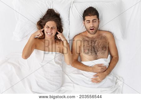 Exhausted Woman Can`t Stand Boyfriend`s Loud Sleep, Plugg Ears With Anger, Suffering From Headache.