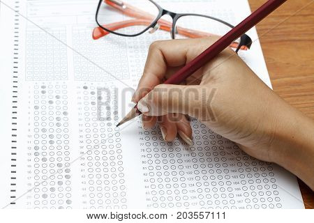 Hand Of Women Holding Pencil On Standardized Test Form With Answers Bubbled In And A Pencil, Focus O